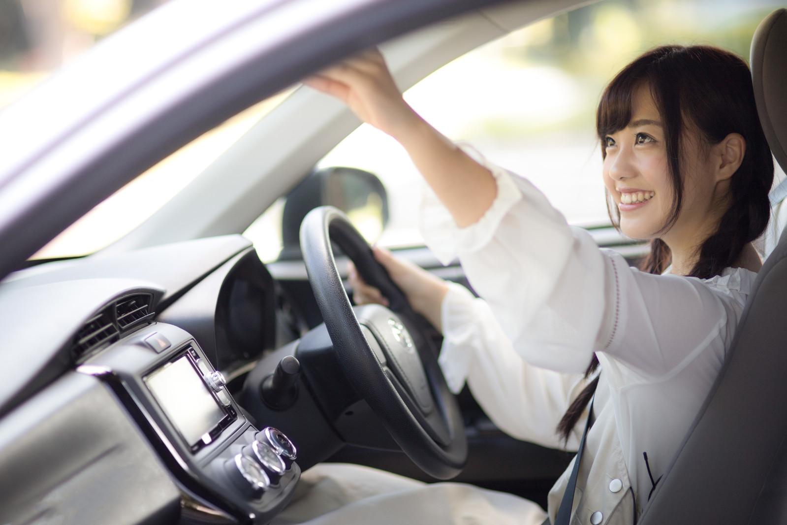 自動車のミラーを確認する女性